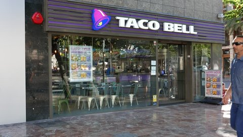VALENCIA, SPAIN - SEPTEMBER 20, 2015: Tourist walking by a Taco Bell fast-food restaurant. Taco Bell serves more than 2 billion customers each year in more than 5,800 restaurants.