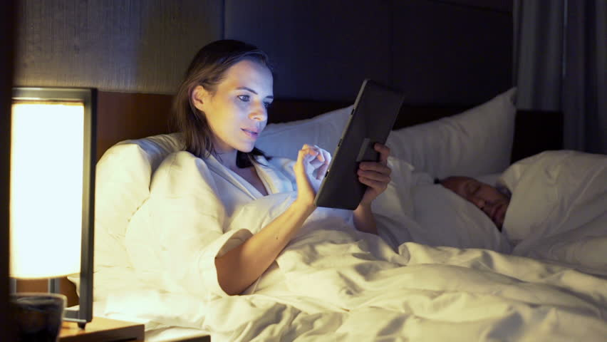 Beautiful Wife Watching Pics On Tablet, Husband Sleeping In Bed Stock Footage Video -7623