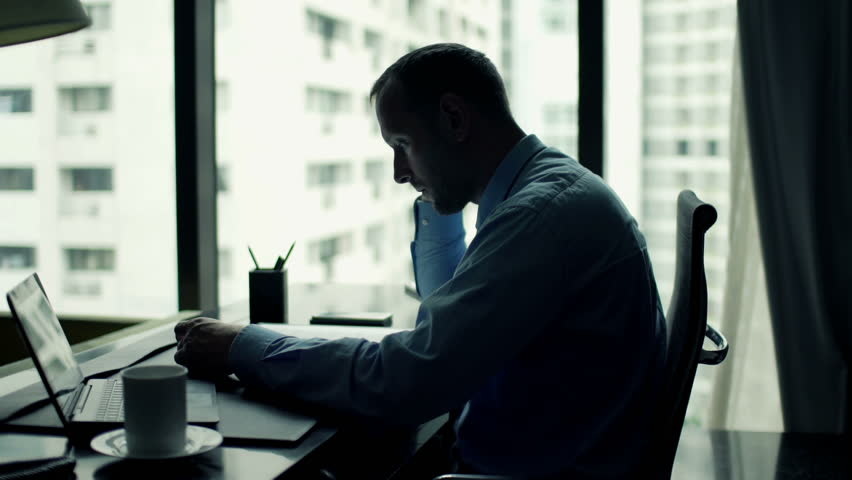 Businessman reading and analyzing documents sitting in the office  | Shutterstock HD Video #11807063