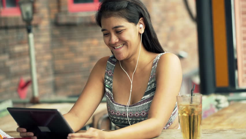 Happy, young woman watching movie on tablet computer sitting in cafe    Shutterstock HD Video #11814422