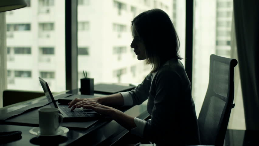Young businesswoman working on laptop sitting by desk in office