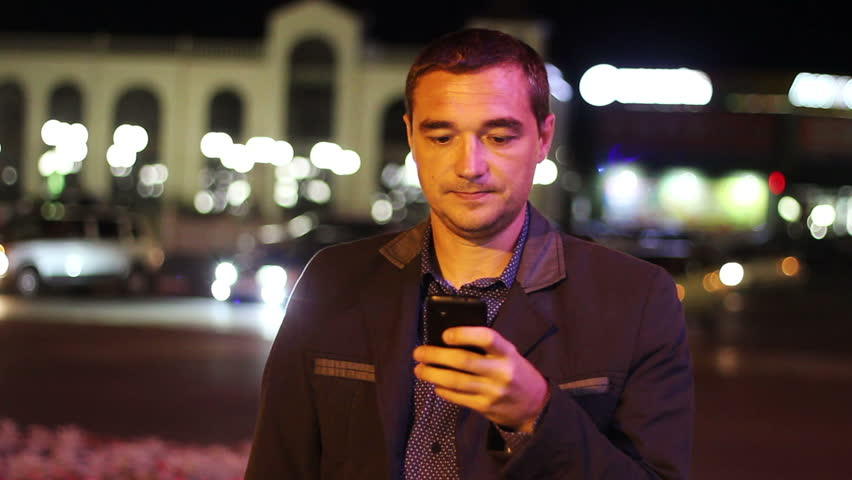 Man sms texting using app on smart phone at night in city. Handsome young business man using smartphone smiling happy wearing suit jacket outdoors.  Urban male professional | Shutterstock HD Video #11848193