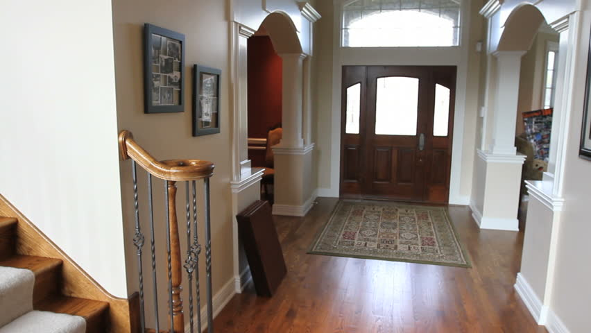 Panning from the main entryway, across the staircase, to the family room in a beautiful luxury house