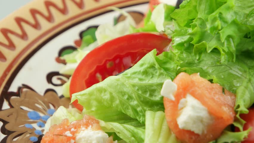 fresh salad with salmon and olives on decorative plate closeup