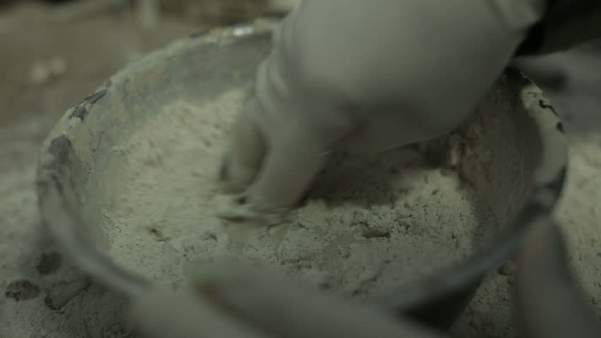 Sculptor in workshop mixing clay to be used on a steel armature #11866403