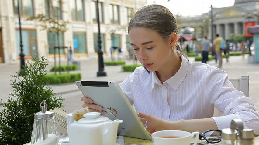 Young Woman Using Her Digital Tablet  and Drinking Tea At A Sidewalk Cafe in Architectural City Center. | Shutterstock HD Video #11879333