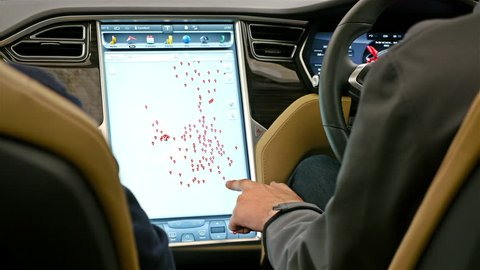 UNITED KINGDOM, LONDON - JUNE 15, 2015: Man showing the newest technology in the automotive industry - computer board system