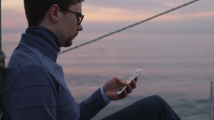 Man is looking and using phone on a sailing boat in the sea at sunset. Shot on RED Cinema Camera in 4K (UHD).
