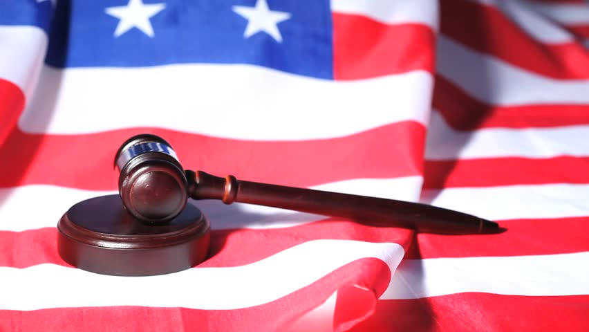 Closeup of a gavel raised on an American flag