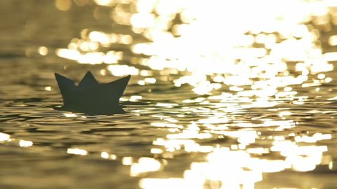 2 in 1 video! The toy paper boat on the surface water by the bright sunlight background. Real time capture. Shot with Red Cinema Camera