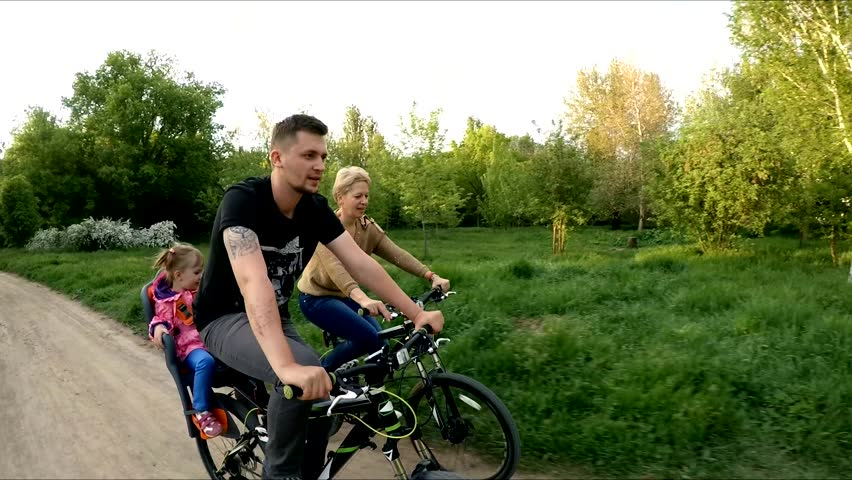 SLOW MO: Side portrait of a young happy family of three - man with little girl sitting on backseat and woman riding bicycles following each other in green park.  | Shutterstock HD Video #11990933