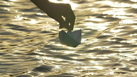 4 in 1 video! The man put paper boat by the bright sunlight reflection on the water surface background. Shot with Red Cinema Camera