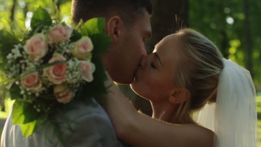 Young bride and groom are kissing in a sunny park. Shot on RED Cinema Camera in 4K (UHD).