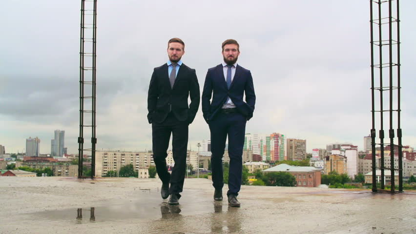 Confident business twins walking in slow motion towards the camera through puddles at construction site