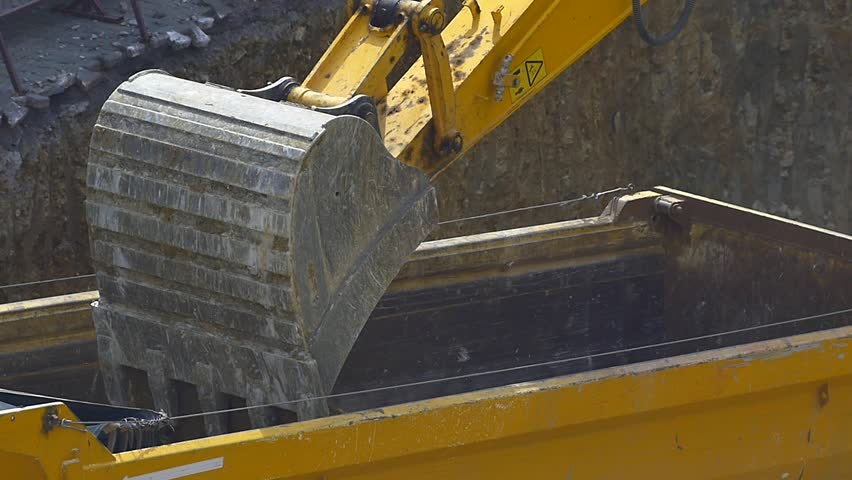Slow Mo. Dump truck being loaded with soil by shovel. Close up, original HD video. Construction machinery working at the construction site