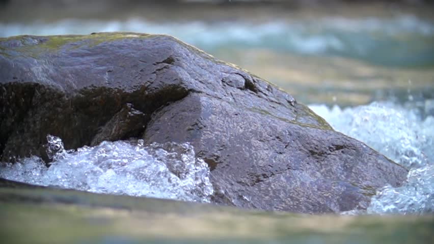 Water in the beautiful mountain river flows round a big stone in slowmotion #12059084