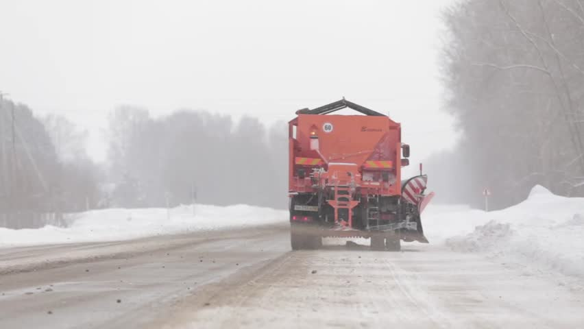 Orange snowplow vehicle featured in winter road sand