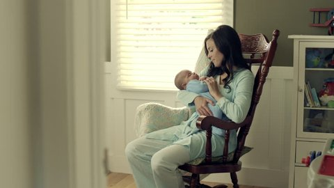 Mother with baby in rocking chair.