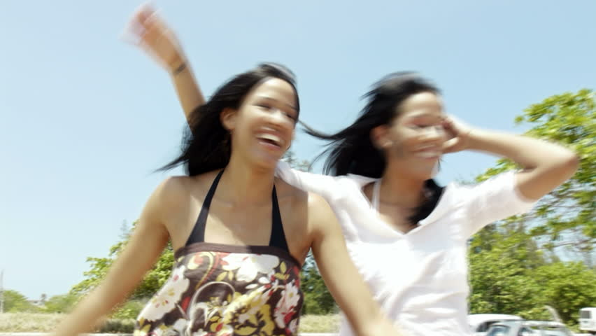 young adult brunette twin women sitting in convertible red car and laughing