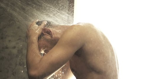 Young man washing hair under shower