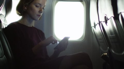 Young woman is using a smartphone inside an airplane next to a window. Shot on RED Cinema Camera in 4K (UHD).