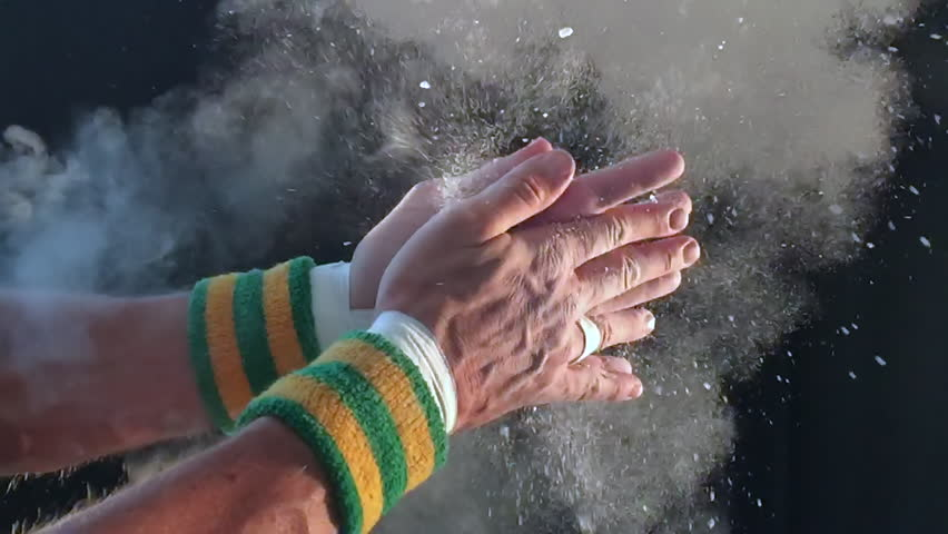 Taped hands of gymnast clapping white chalk powder into a slow motion cloud against dark background