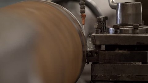Slow motion, close in shot of high speed metal/steel lathe milling metal with water jet cooling