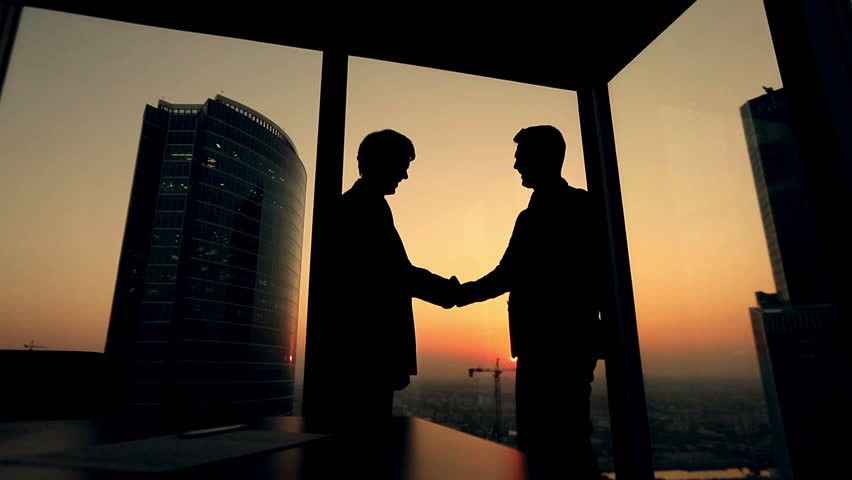 Silhouette of two businessmen talking and shaking hands standing by the window at sunset, the construction of a skyscraper and crane in the background | Shutterstock HD Video #12178613