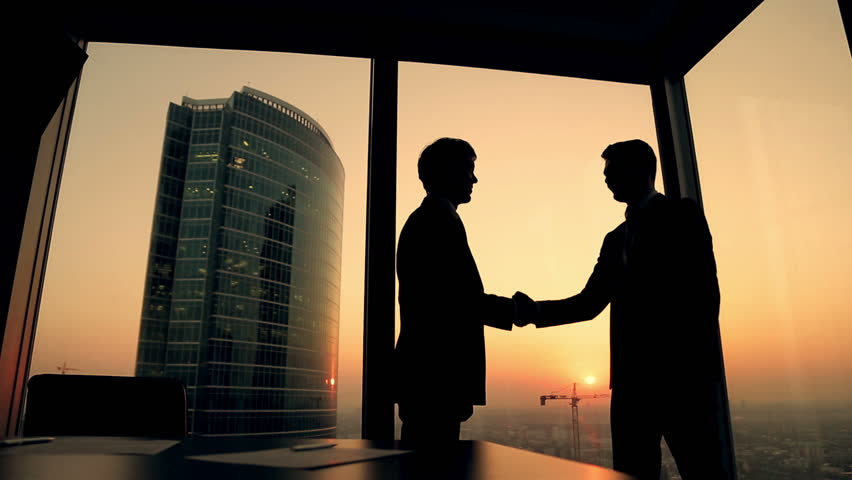 Silhouette of two businessmen talking and shaking hands standing by the window at sunset, the construction of a skyscraper and crane in the background