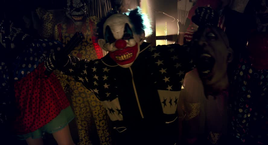 Halloween party horror clowns. The scary clown standing in the midst of a terrible clown with a severed head zombie.