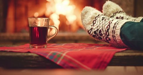 Woman relaxes by warm fire in woollen socks and having a cup of hot tea. Close up on feet. Cozy evening by the fireplace during the cold season. Slow motion 120 fps. Dolly shot. 4k graded from RAW.