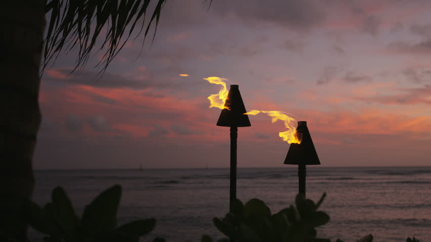 Torches with fire and flames burning in Hawaii sunset sky by palm trees. Beautiful slow motion torches on Hawaiian Waikiki beach, Oahu. RED EPIC SLOW MOTION | Shutterstock HD Video #12193856