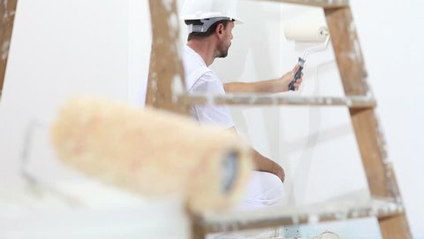 painter man at work, with roller painting wall, and wooden ladder in close up
