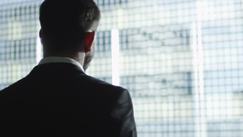 Businessman in a suit looks out of a big window in a city on a sunny day. Shot on RED Cinema Camera in 4K (UHD).