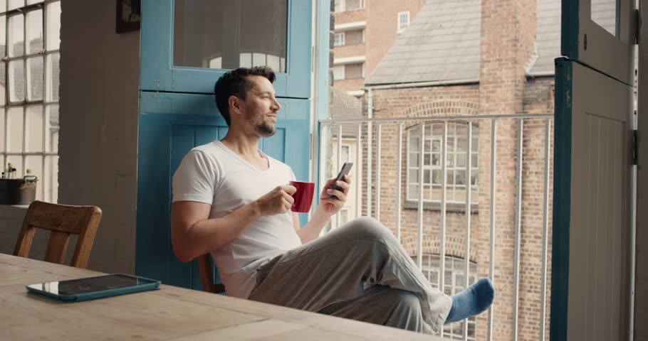 Handsome man at home drinking coffee using smartphone loft apartment in pajamas relaxing | Shutterstock Video #12270185