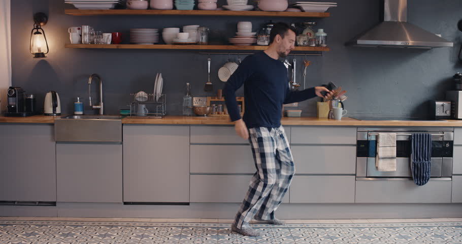 Happy young man dancing in kitchen wearing pajamas in the morning listening to music on smartphone and coffee at home