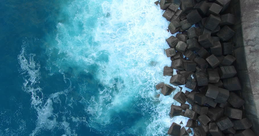 AERIAL (top view). Flight above ocean shore of Tenerife. Deep turquoise water, white spray and dark stone cubes pier. Abstract video background for titles. 4K