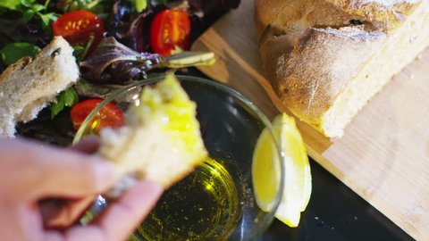 4K Hands breaking bread  and dipping a piece into fresh olive oil and balsamic vinegar dressing. Shot on RED Epic.