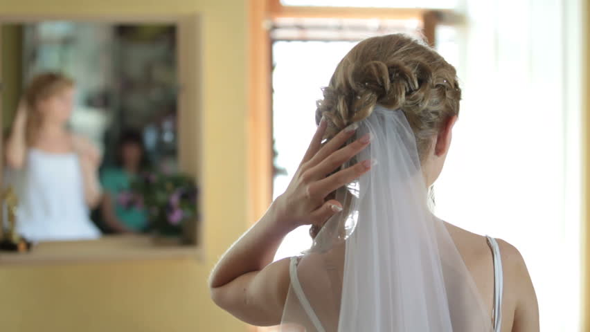 Bride sits before a mirror in the morning of the wedding day