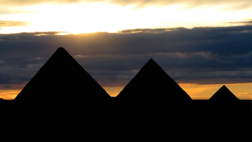 Pyramids in Egypt with cloudy dusk in the background.