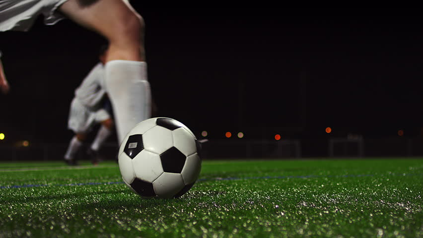 Close up of a soccer ball being kicked in slow motion at night #12304703