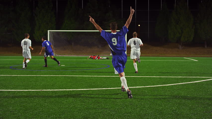 Soccer players pass the ball down the field at night and make a goal and celebrate   Shutterstock HD Video #12305066
