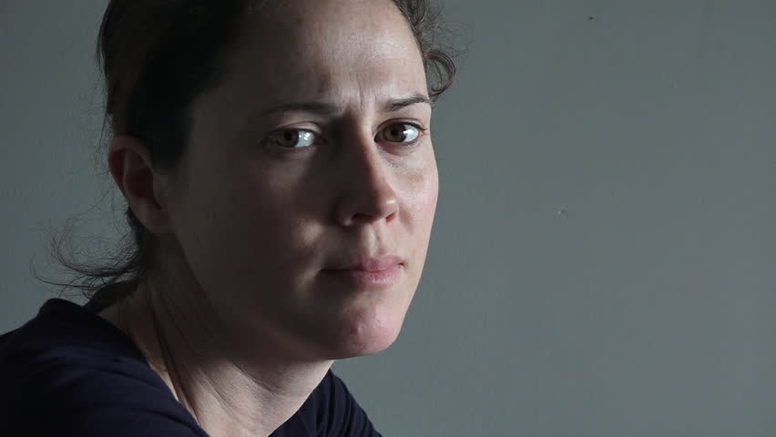 Caucasian woman in her thirties (30s) sitting at a table upset looking at the camera. Woman concept (slider motion) copy space