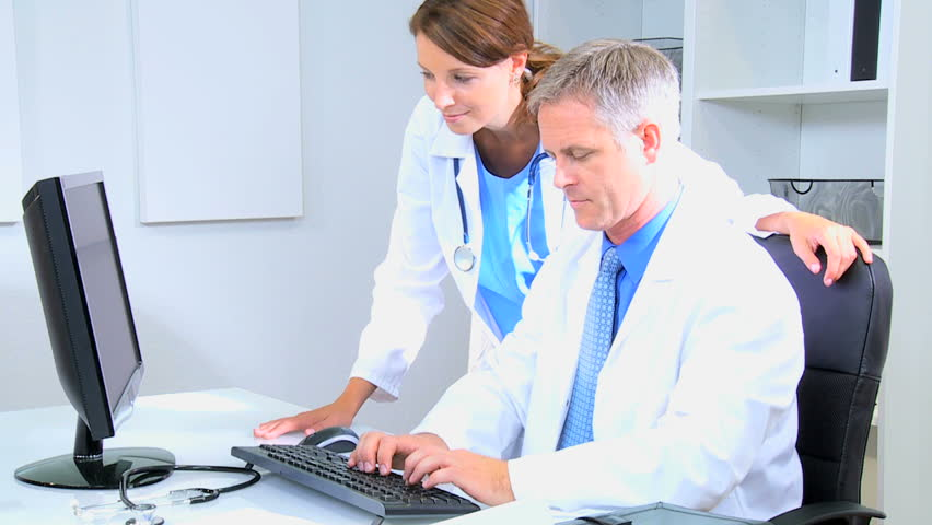 Caucasian male female doctor consultant indoors medical hospital white coats planning cloud technology computer device tests | Shutterstock HD Video #12355613