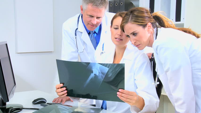 Young Male Female Hospital Doctors Consulting Over Patient X-ray ...