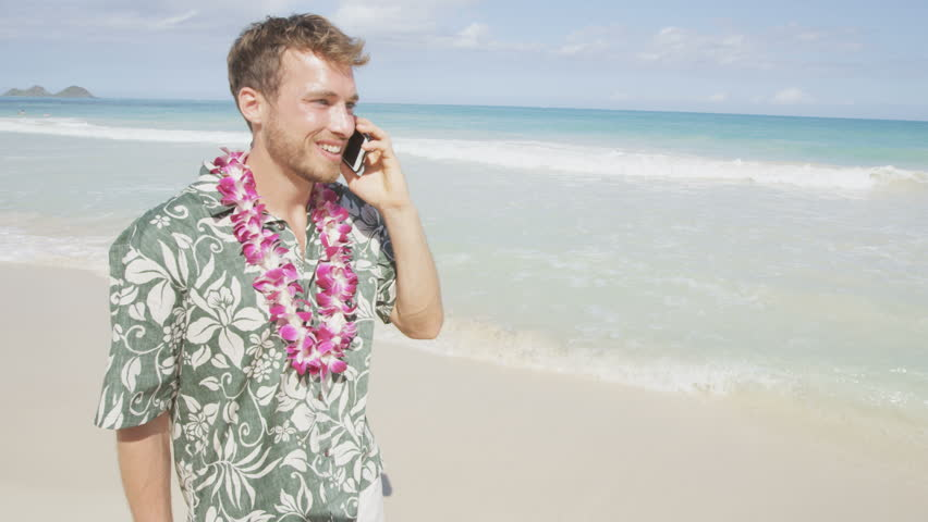 Man talking on smart phone on Hawaii beach having conversation on smartphone. Young business man working on vacation travel. Urban male professional in Hawaiian clothing and Aloha shirt and lei. | Shutterstock HD Video #12365951