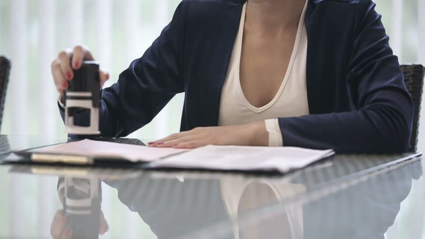 Attractive african american business woman puts a seal on the contract. Slow motion. Close up