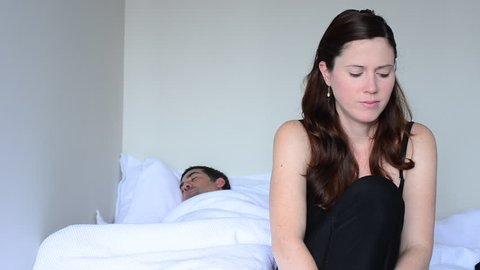 Upset young woman in her thirties (30s) having problems with sex. Focus on the woman in the foreground and the man in bed in the background. Sex and relationship concept