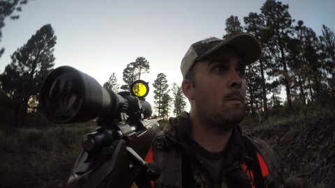 A hunter walks quietly through a forrest hunting deer with his rifle