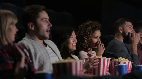 Cinema, entertainment and people concept - happy friends watching movie in theater. Couple and other people eating popcorn and drinking soda while watching movie at the cinema.